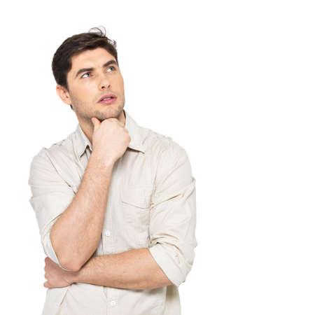 hombre pensando: Retrato del hombre de pensamiento joven mira para arriba en casuals aislados sobre fondo blanco. Foto de archivo