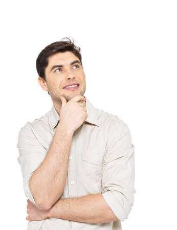 Portrait of the young smiling  thinking man looks up  in casuals isolated on white background. photo