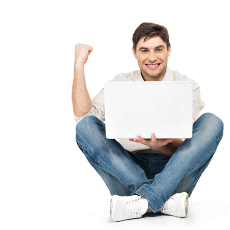 casuals: Portrait of  happy successful man working on laptop  in casuals - isolated on white. Concept communication.