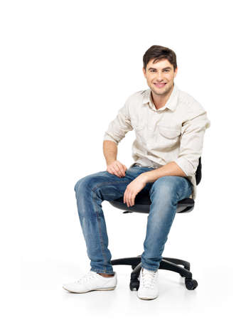 sits on a chair: Portrait of smiling happy man sits on the office chair isolated on white.