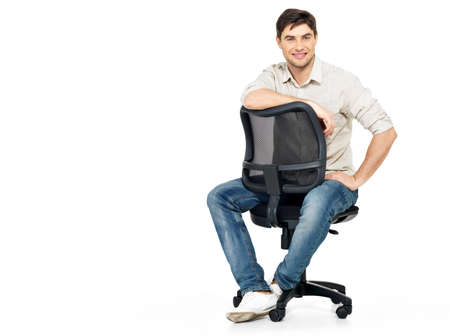 man in chair: Portrait of smiling happy man sits on the office chair isolated on white.