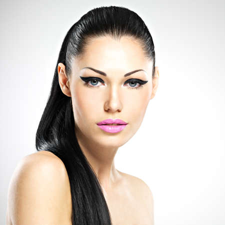 Face of the beautiful woman with fashion makeup. Sexy girl with pink lips - isolated photo