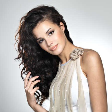 voluptuosa: Joven y bella mujer con el pelo largo y castaño. Bonito modelo plantea en el estudio.