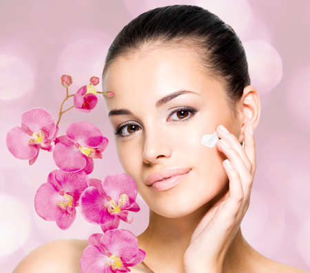 Beautiful woman applying cosmetic cream  on face with flowers. Skin care concept. photo