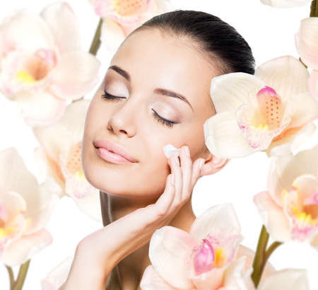 Beautiful woman applying cosmetic cream  on face with flowers. Skin care concept. Stock Photo