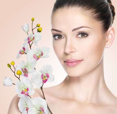 beautiful face: Adult woman with beautiful face and white flowers. Skin care concept. Stock Photo