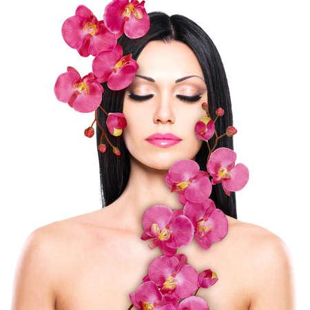 orchidee: Giovane donna con il bel viso e fiori freschi. La cura della pelle concetto.