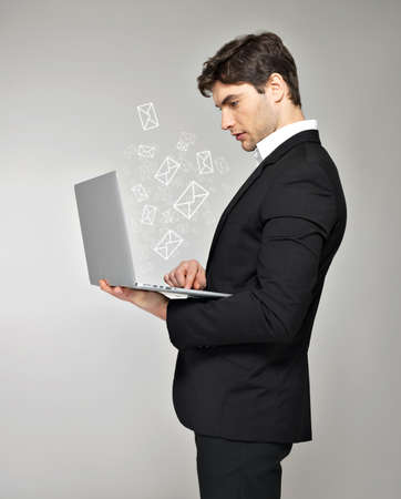 Business man with laptop in hand and mail icon over grey background photo