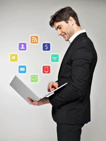 Business man with laptop in hand and media icon over grey background photo
