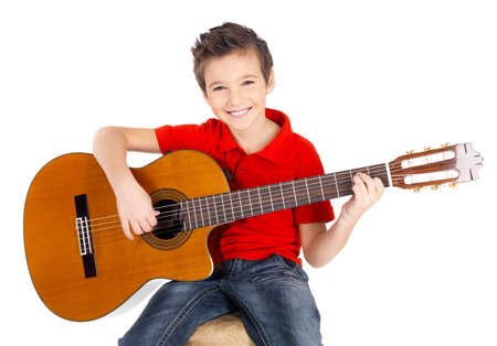a guitarist boy playing guitar: Handsome happy  boy is playing on acoustic guitar - isolated on white background Stock Photo