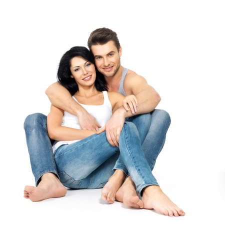 undershirt: Beautiful happy couple in love on white background dressed in blue jeanse and white undershirt
