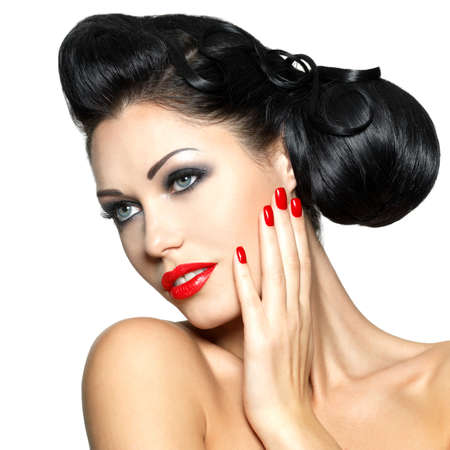 finger on lips: Beautiful fashion woman with red lips, nails and creative hairstyle - isolated on white background