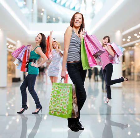 Happy beautiful women with shopping bags stands at shop photo