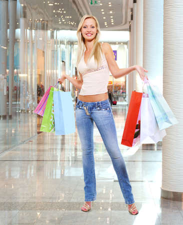 Happy beautiful woman with shopping bags stands at shop Stock Photo - 22095360