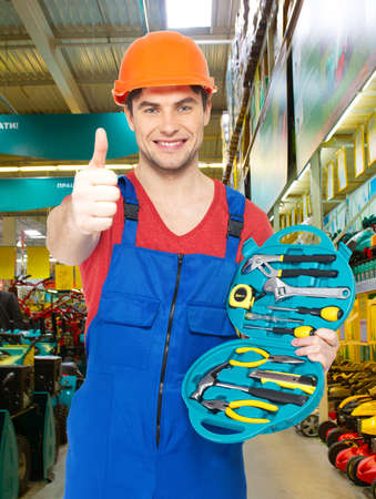 Portrait of happy handyman with tools showing thumbs up sign  photo