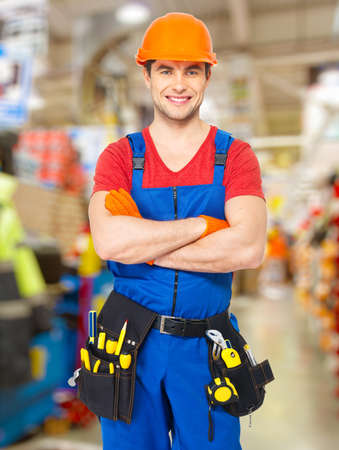 constructor: Portrait of smiling handyman stands at store