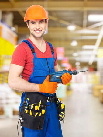 Portrait of smiling handyman with drill at   warehouse photo