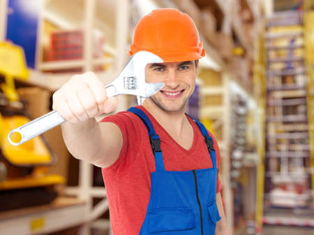 Portrait of smiling worker with big spanner  photo