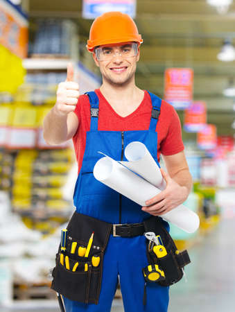 Portrait of smiling handyman with tools and paper showing thumbs up sign  stands at warehouse photo