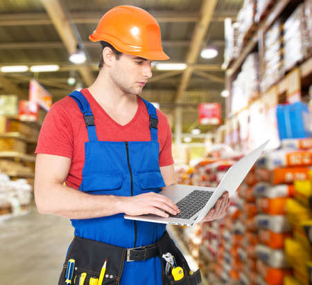 Portrait of smiling handyman with laptop working warehouse Stock Photo - 20222813