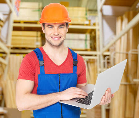 Portrait of smiling handyman with laptop working warehouse photo