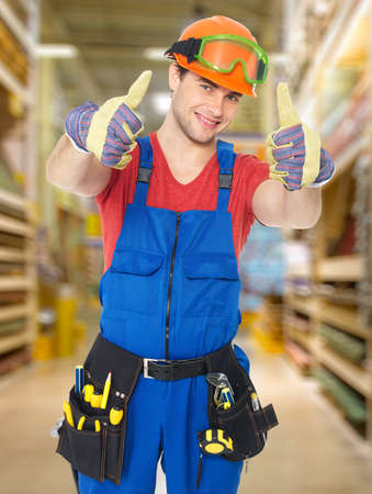 professional young worker with thumbs up sign at shop photo