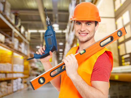 Portrait of smiling manual worker with tools at warehouse Stock Photo - 20222811