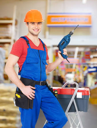 Portrait of smiling manual worker with tools at warehouse photo
