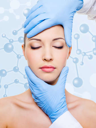 beautician touching attractive health woman face. beauty treatment of skin photo