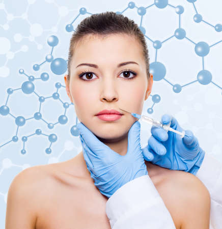 Injection of botox in beautiful woman face over molecule background photo