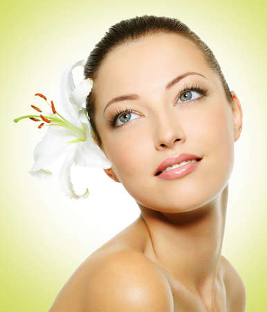 Beauty face of the young beautiful woman with flower Stock Photo