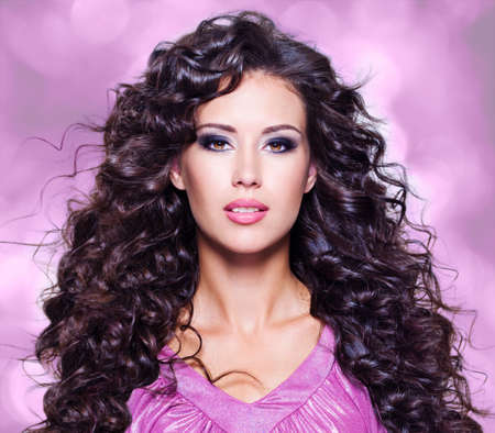 Face of  a beautiful young woman with brown long ringlets hairs and fashion makeup Reklamní fotografie