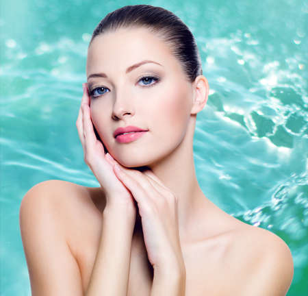 Close-up portrait of sexy beautiful young woman with fresh skin of face over water background