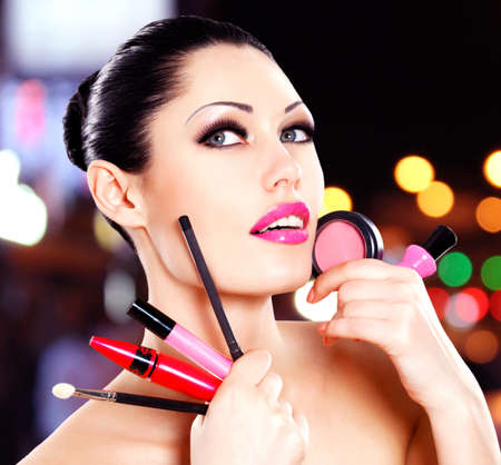 Beautiful woman with makeup cosmetic tools near her face.  Stock Photo - 22109792