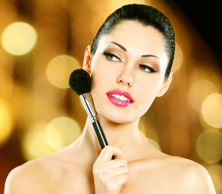 Portrait of  beautiful woman applying blusher on face using cosmetic brush photo