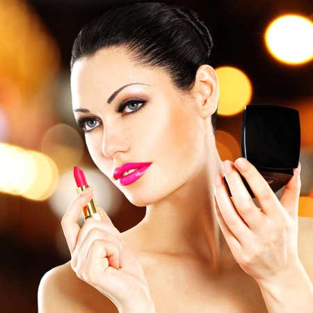 Beautiful woman makes makeup applying pink lipstick on lips. Stock Photo - 22109795