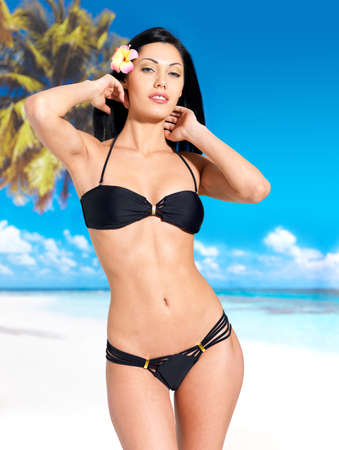 Woman with beautiful body in black bikini sunbathe on the beach photo
