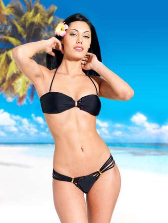 Woman with beautiful body in black bikini sunbathe on the beach