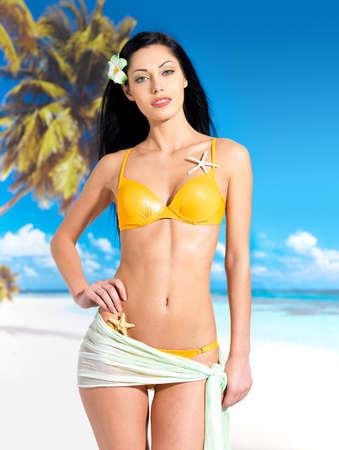 yellow bikini: Donna con bel corpo in bikini giallo in spiaggia Archivio Fotografico