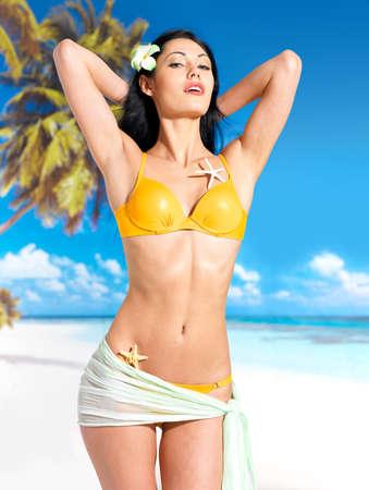 yellow bikini: Donna con bel corpo in bikini giallo sulla spiaggia
