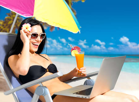 sun umbrella: Happy woman on the beach with a laptop computer. Vacation and communication concept.