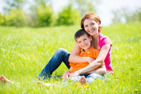 kids hugging: Happy mother and son in the spring meadow outdoor portrait Stock Photo