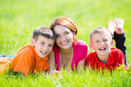 Young happy mother with children in park -  outdoor portrait photo