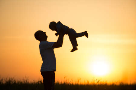 Happy dad throws the baby at sunset  Stock Photo