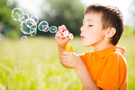 Young caucasian boy blowing the soap bubbles on nature photo