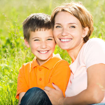 Happy mother and son in the spring meadow outdoor portrait photo