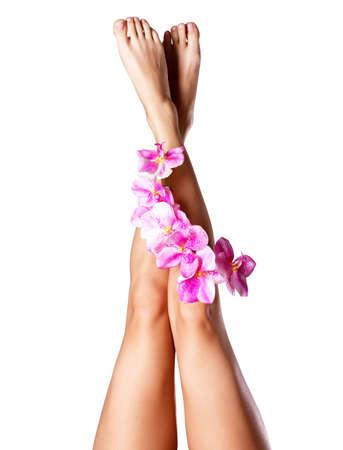pied jeune fille: Longues et belles jambes de femme avec une fleur. Concept de soins de beaut?