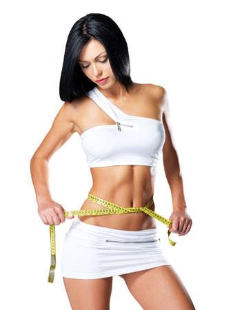 Slim woman and measure tape around her body - a studio shot