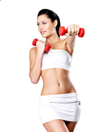 beautiful young woman with dumbbells -  grey studio background. Healthy lifestyle concept.