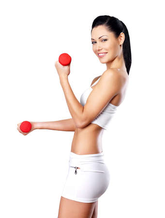 beautiful happy woman with dumbbells -  grey studio background. Healthy lifestyle concept.